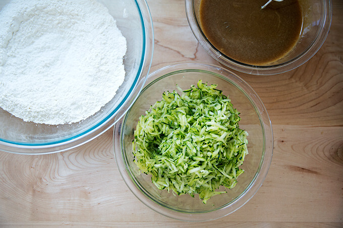 Components to make zucchini bread: dry ingredients, wet ingredients, grated zucchini.