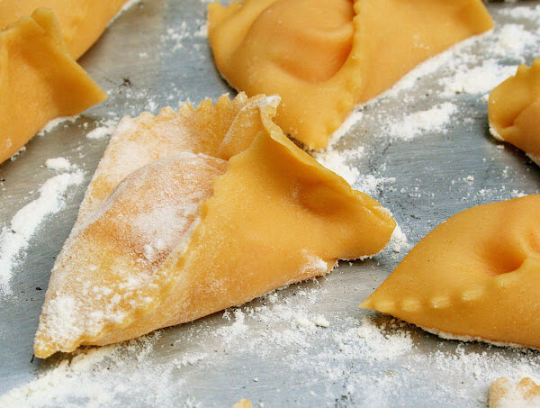 A sheet pan filled with uncooked pumpkin ravioli.