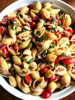 This simple pasta salad is particularly good warm, when the just-boiled shells melt the cheese, just slightly cook the tomatoes and soak up all the flavors of the olive oil and lemon juice. It can also be prepared ahead and served at room temperature — it tastes better the longer it sits in fact. // alexandracooks.com