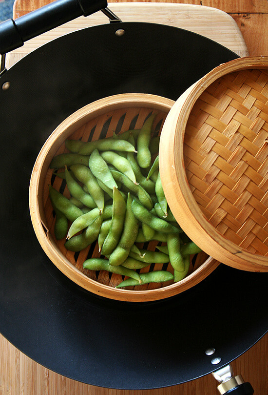 Edamame steaming in a bamboo steamer basket in a wok.