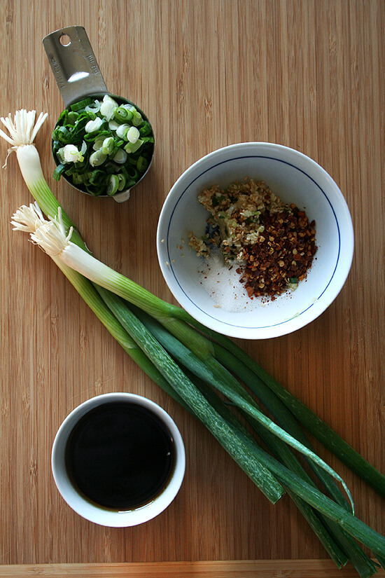 A board of scallions, spices, and soy sauce.