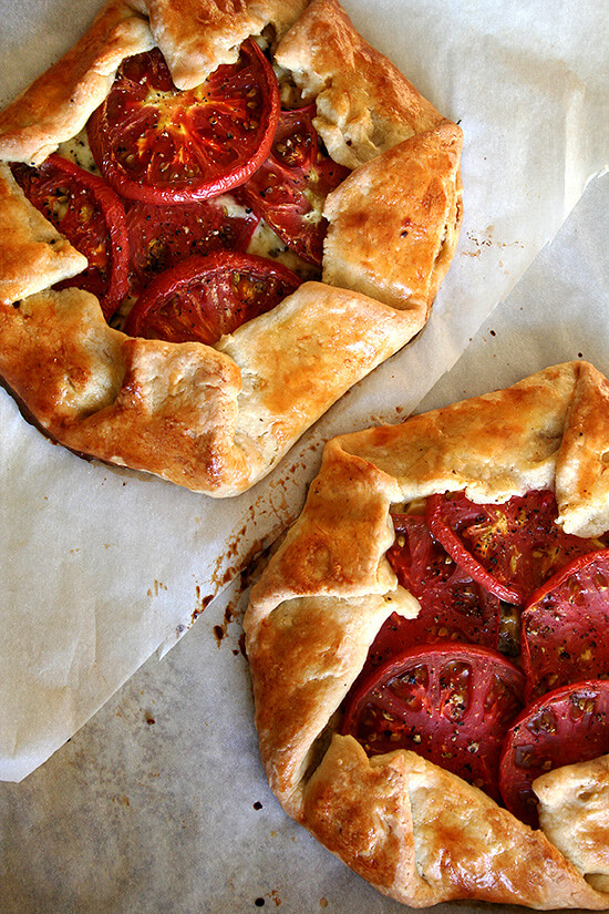 A sheet pan with two freshly baked savory galettes.