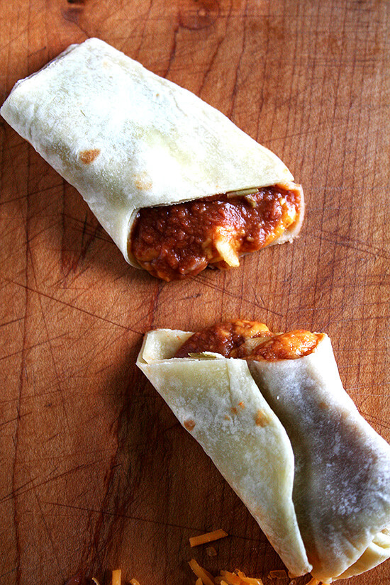 A halved bean and cheese burrito made with homemade flour tortillas on a board.
