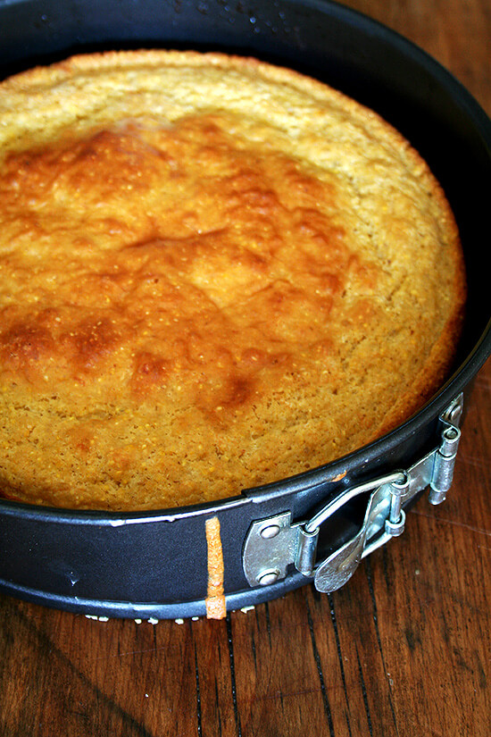 Buttermilk Cornbread baked in spring-form pan sitting on wooden surface