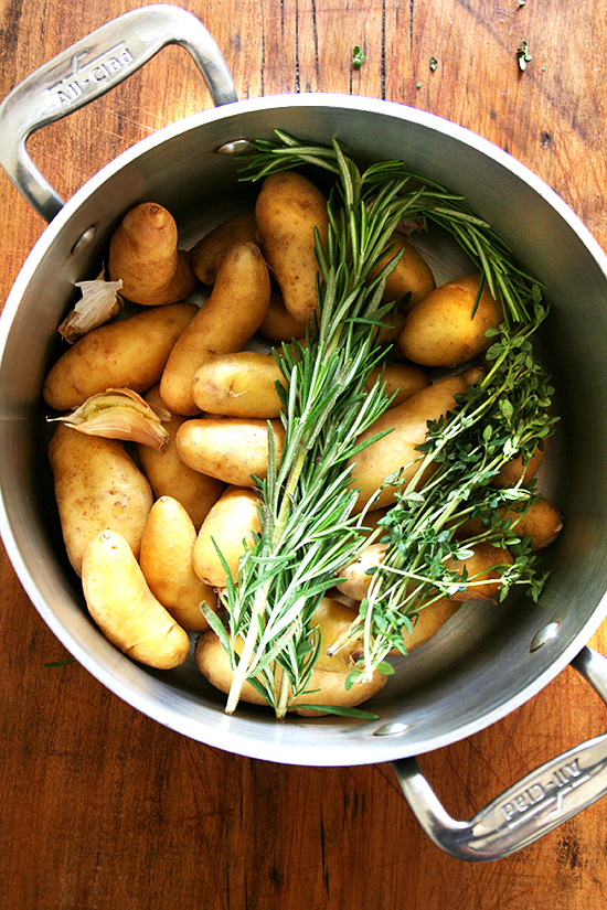 A pot filled with potatoes, herbs, and garlic.