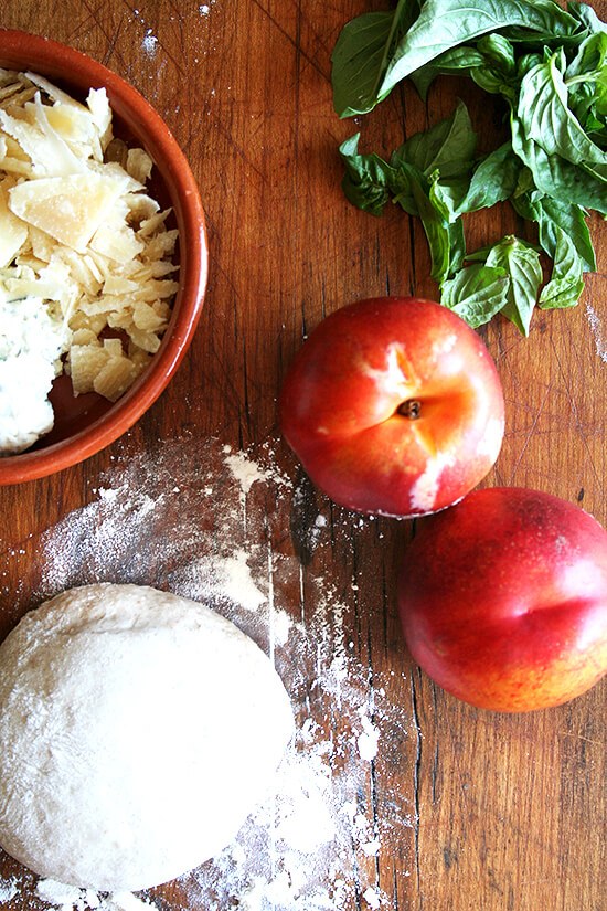 Nectarine pizza ingredients on a board.