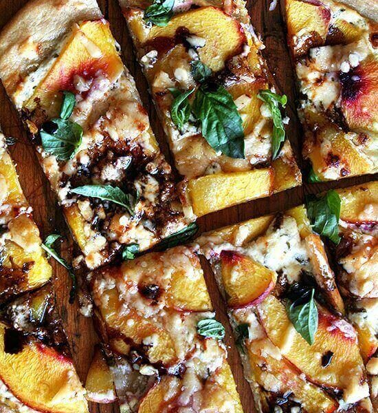 Just-baked nectarine pizza sliced into pieces.