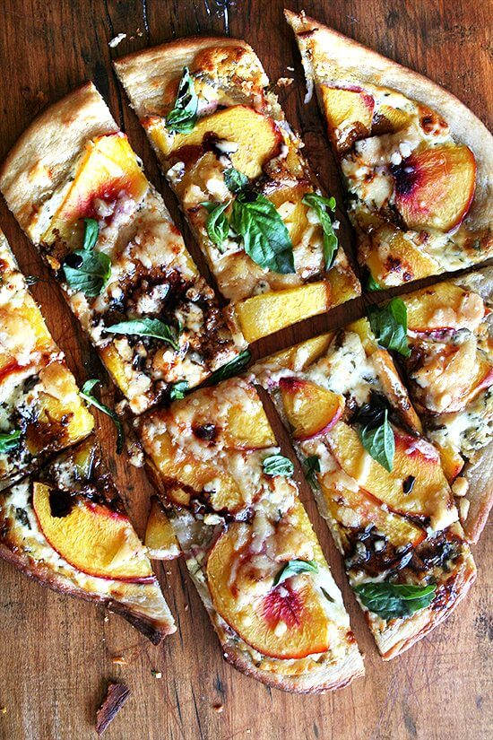 Just-baked nectarine pizza on a board, sliced into pieces.