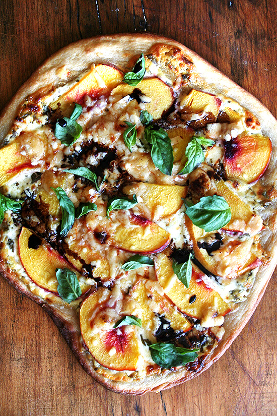 Just-baked nectarine pizza on a board with reduced balsamic.