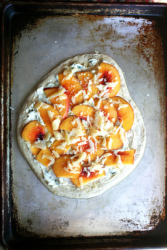 Assembled nectarine pizza on a sheet pan.