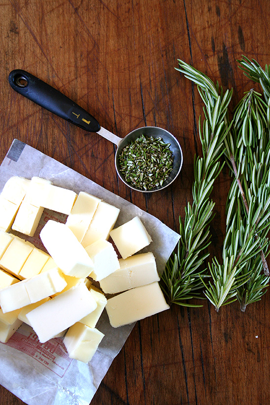 Ingredients for rosemary shortbread on a board: butter + rosemary.