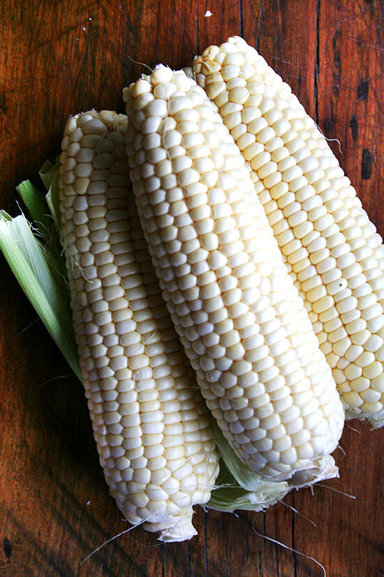Four ears of corn on a board.