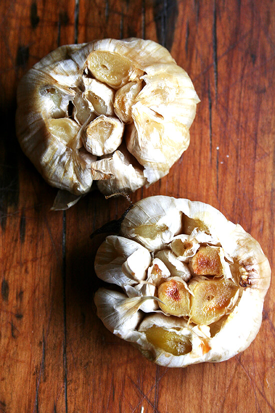 An overhead shot of two heads of roasted garlic.