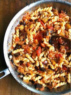 A sauté pan filled with roasted eggplant pasta with caramelized onions and tomatoes.