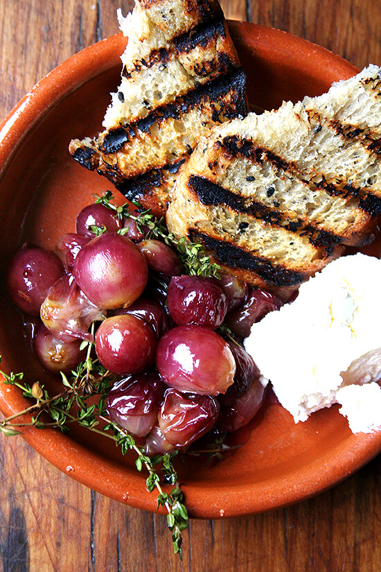 This recipe for thyme-roasted grapes with ricotta and grilled bread couldn't be more simple or delicious. Thyme-infused roasted grapes atop grilled bread spread with homemade ricotta makes for a delectable lunch, hors d'oeuvres, or side dish. // alexandracooks.com