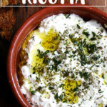 A bowl of homemade ricotta with herbs, olive oil, and grilled bread.
