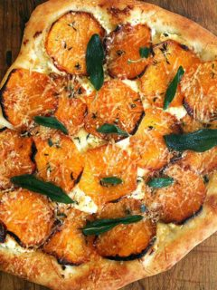 A roasted butternut squash and crispy sage pizza on a board.