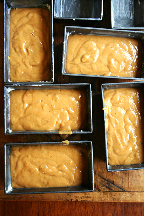 Five mini loaf pans filled with pumpkin bread batter.