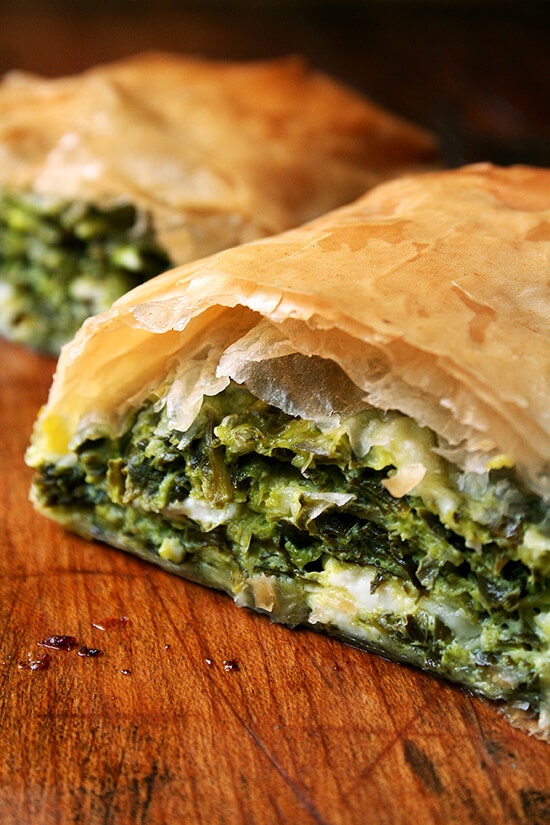 A halved spanakopita strudel on a board.