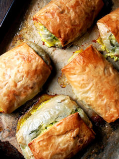 Five baked spanakopita strudels on a sheet pan.