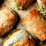 A sheet pan of just-baked spanakopita strudels.