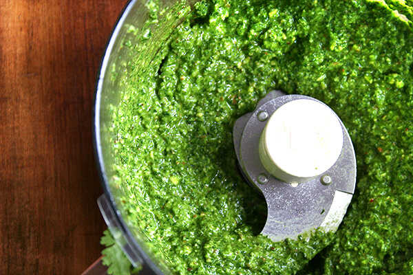 Food processo with pesto sauce puréed.