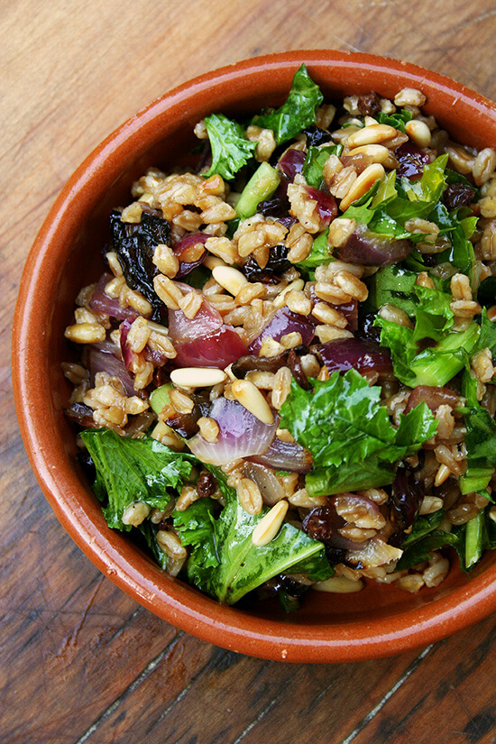 A bowl of farro salad with roasted onions, toasted pine nuts, and wilted mustard greens.