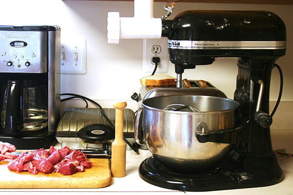 A stand mixer with a meat grinder attached.