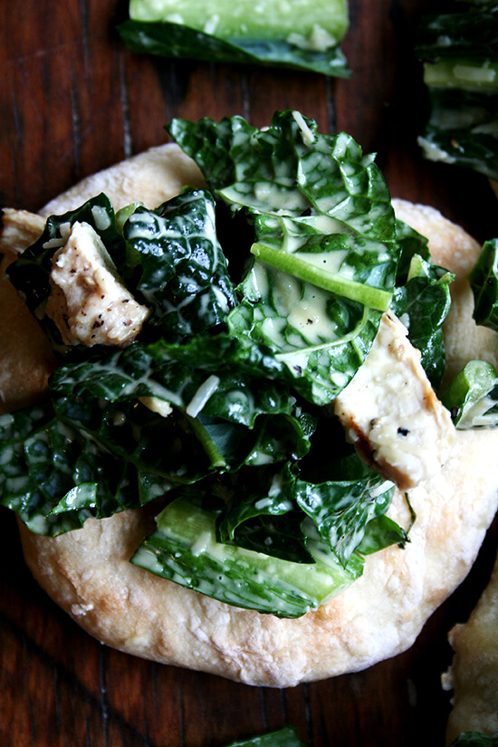 """I'm planning a dinner party and thought it might be fun to make little flatbreads — """"piadines"""" I saw them called — piled high with caesar salad — boring, I know, but perhaps made interesting by kale — tossed with sliced grilled chicken breasts — boring, I know, but chicken caesar kale salad is safe. I love this kind of thing, when bread and vegetable and meat are all wrapped up in one casual, fun, summery, light dish. // alexandracooks.com"""