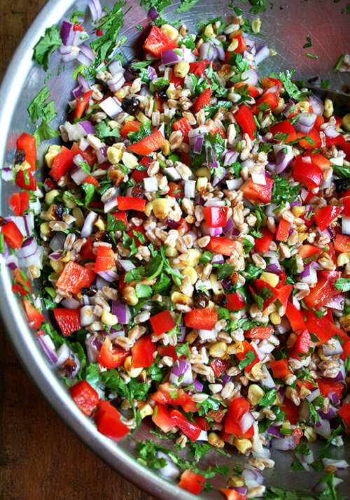 This farro salad, a combination of roasted corn, fresh-squeezed lime juice, cilantro, minced chili peppers and diced peppers and onions, has become a weekly staple. If you strategize by chopping the vegetables and herbs while the corn is roasting and the farro is simmering, this salad can come together in just about 20 minutes. It yields a lot, thanks to all of the add-ins, and tastes better with each passing day. // alexandracooks.com