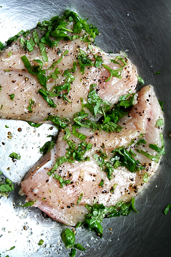 uncooked chicken breasts seasoned with basil, salt and pepper