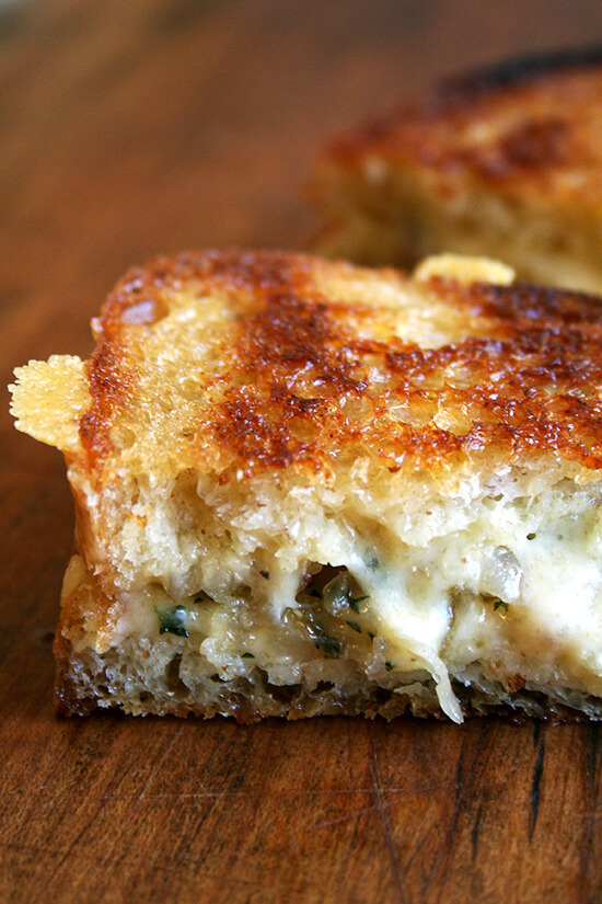 This amazing recipe for a classic grilled cheese sandwich calls for crisping country white bread slices in a skillet on one side before topping them with cheese and sautéed shallots. The open-faced halves finish cooking in the oven before being pressed together into a traditional sandwich. This simple technique produces such a brilliant result: perfectly golden bread flanking perfectly melty cheese. // alexandracooks.com