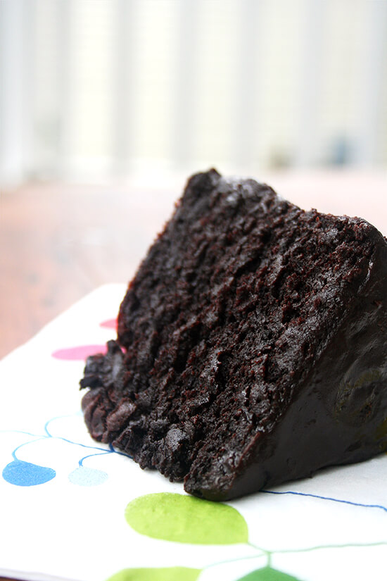 A of slice of double chocolate cake with black velvet icing on a napkin, ready to eat.
