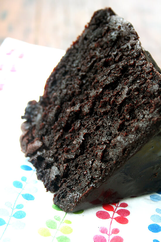 A slice of double chocolate cake with black velvet icing on a napkin.