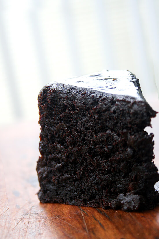 A slice of double chocolate cake standing on a board.