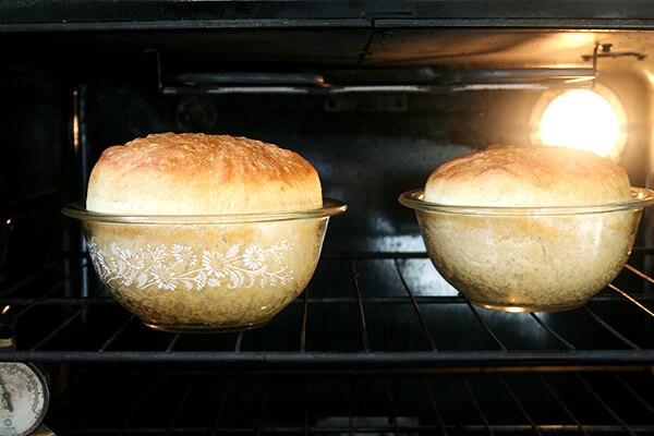 Two loaves of peasant bread baking in oven-safe glass bowls