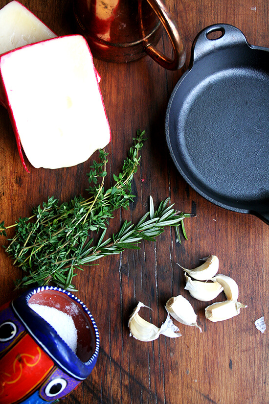 ingredients for baked fontina on a board: fontina, rosemary, thyme, garlic, olive oil, salt.