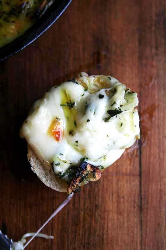 A bite of baked fontina with rosemary and thyme on bread.