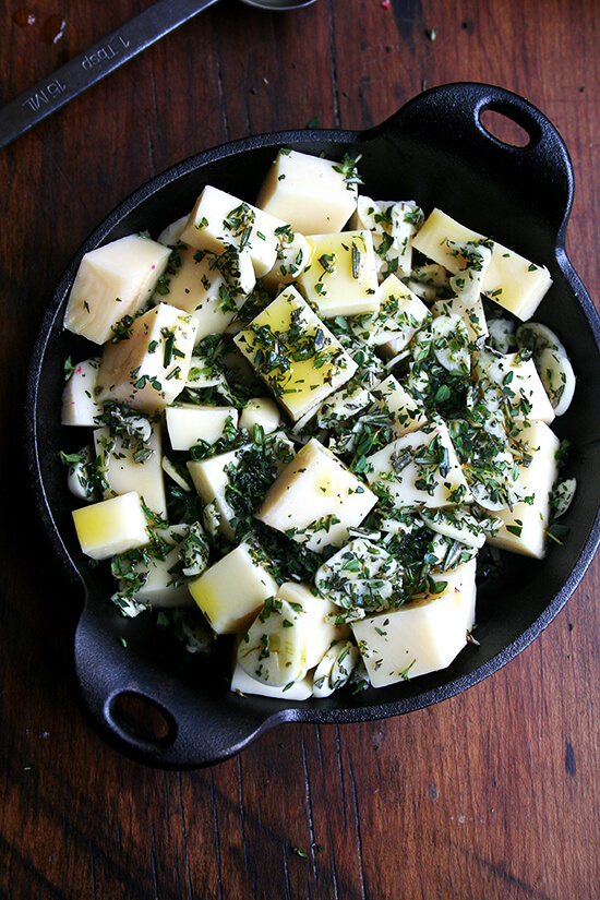 cubed fontina, herbs, olive oil, garlic & salt in a cast iron skillet on a board.