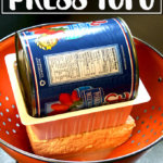 A homemade tofu press with a colander and a can of tomatoes.