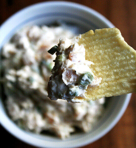 A bowl of real sour cream and onion dip aside Ruffle potato chips