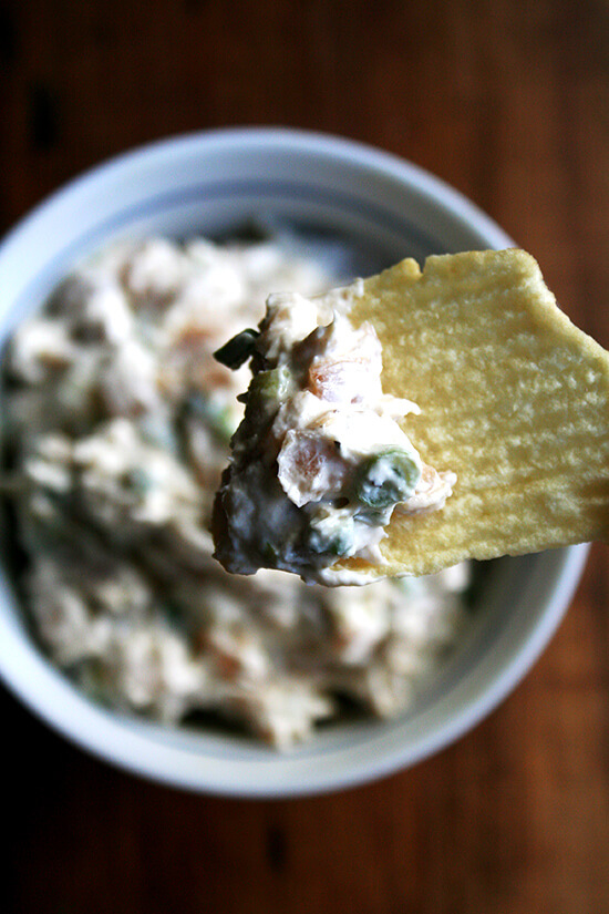 A bowl of real sour cream and onion dip with a Ruffle potato chip.