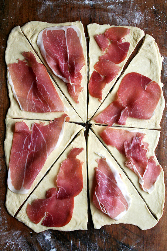 topping triangles with prosciutto