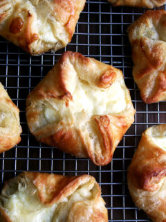 A cooling rack of just baked cheese danishes.