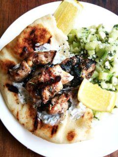 A platter of chicken souvlaki with lemon, tzatziki, cucumber salad, and pita.