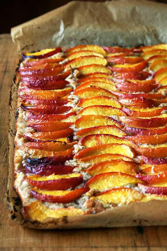 For this peach frangipane tart, my favorite galette dough is used for a sheet-pan tart. After smearing the whole batch of frangipane over its surface and arranging half a dozen sliced peaches over top, the fruit is brushed with melted butter and sprinkled with sugar. Forty minutes later, the tart emerges from the oven, slices of fruit glistening, frangipane bubbling through the crevices. // alexandracooks.com
