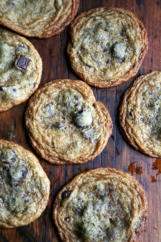 Thin and chewy chocolate chip cookies on a board.