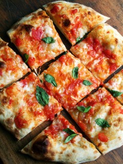 A margherita pizza cut into pieces.