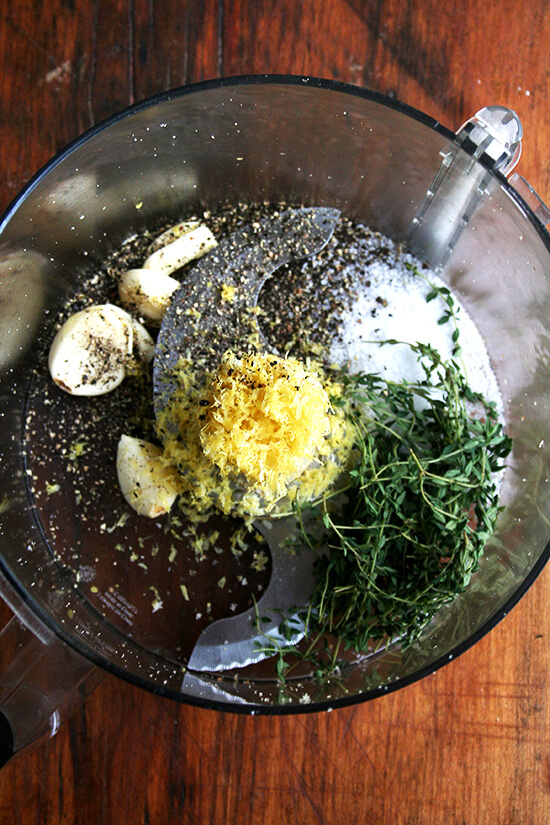 Food processor with lemon zest, garlic, salt, pepper, and thyme — this seasoning mix will flavor the bread crumbs.