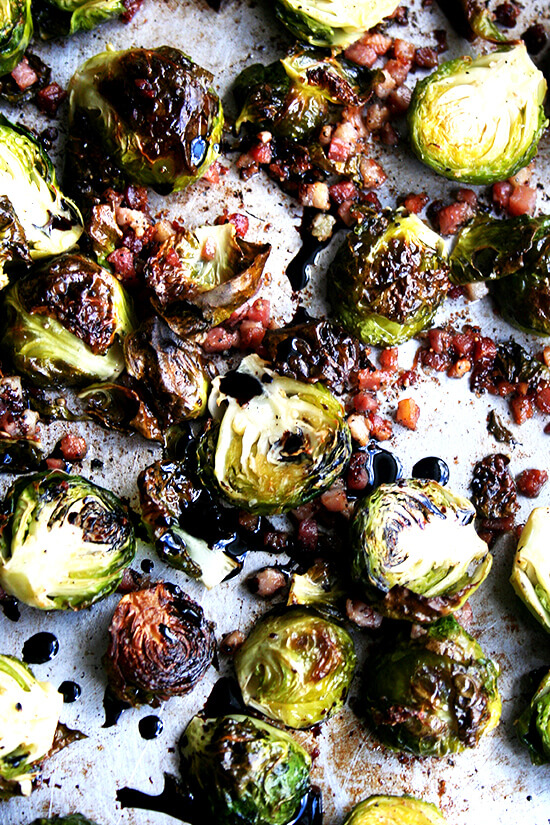Close-up view of adding the balsamic reduction to the brussel sprouts in a sauce pan.
